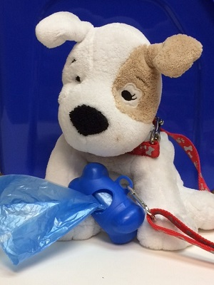 Stuffed dog with leash bag dispenser